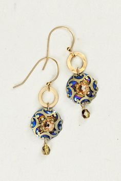 """Encounter a fascinating display of true artisan craftsmanship when you wear our Encircled Abela Earrings. Featuring enthralling layers of detailed cutwork and a dazzling center gemstone this earring's enchanting motif is exquisitely accented with a hand-hammered ring and scintillating crystal teardrop bead.    Swarovski crystal  Gold overlay  Niobium  Antiqued brass  Bohemian glass  Gold overlay ear wires  1 3/4"""" l. x 1/2"""" w. Earrings by Holly Yashi. Accessories - Jewelry - Earrings New York…"""