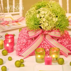 fun idea.  flower base to the flower centerpiece.  like how the ribbon of the centerpiece is tied into the napkin tie then coordinating the pink glass and green glass and the touch of limes.  could be done if other color schemes