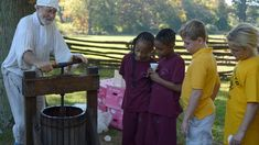 Students learn how to press apples into cider at Pennsbury Manor's Harvest Day