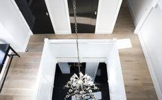 Grijs eiken met zwarte deuren en witte kozijnen combineert mooi