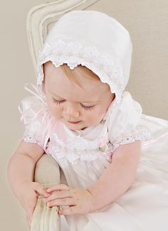 Gentle touches of pale pink take our graceful Tess silk baptism gown from simply pretty to truly exceptional. set includes gown, cotton slip, and bonnet Color: pearl white (a rich, … Catholic Christening, Christening Gowns For Girls, Baptism Gown, Cotton Slip, How To Make Ribbon, Pink Flowers, Toddler Girl, Silk, Baby Care