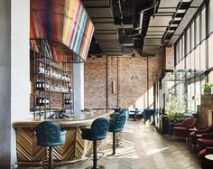 The hotel bar at The Williamsburg Hotel in Brooklyn, New York features exposed brick and original parquet flooring. Photography by Annie Schlechter.