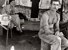 """Oregon, August 1939. """"Unemployed lumber worker goes with his wife to the bean harvest. Note Social Security number tattooed on his arm."""