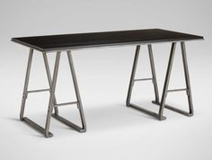 Tompkins Desk Taking its cues from casual, industrial design, this desk's silhouette is a nod to modern sawhorse design. Its square, steel base in a washed zinc finish is topped with a solid oak top. The top is available in an array of beautiful finishes.