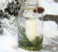 une bougie blanche mise dans un pot en verre décoré de pommes de pin