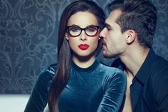 Confident sexy woman with red lips seducing young rich man