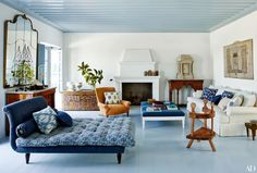 A kicky Kathryn M. Ireland print dresses up the family room's double chaise longue; an Irini Gonou collage is mounted above the sofa, and the captain's chair in the foreground and the painted chest at rear left are Greek antiques.