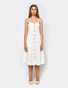 Casual dress from Farrow in Ivory. Sweetheart neckline. Adjustable thin straps. Front button closure. Smocked back. Wasted. Full skirt. Front patch pockets. Straight hem. Lined. Mid length.   • Woven Cotton shell, Broadcloth lining • 100% cotton • Han