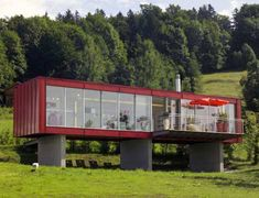 Love this shipping container home because of it's concrete piers, all the glass and the neat deck. Love the pretty setting too.