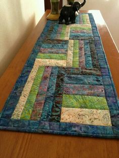 Tapete- How to: Quilt along long lines center to boarders, vertical and horizontal. Once each block is anchored, stitch each pieced seam. A walking foot can help keep seams flat.
