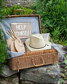 wicker picnic valise filled with fans (and hats for the guys...love this!) #wedding
