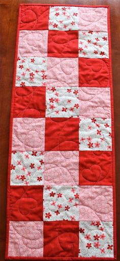 "This fun quilted table runner was made by two friends who love to quilt together. It was created with fabrics from Sandy Gervais's LAmour fabric line for Moda. The fabric features flowers and circles in red, pink, brown and cream. This table runner measures approximately 35.5"" by 13.5"" and is the perfect size to decorate your dining room table, coffee table, or any other surface that you want to add a splash of color to. The backing is a marbled red fabric from Moda.  This table runner was…"
