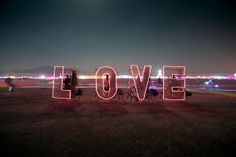 L-O-V-E, Four bikes, each carrying side panels illuminated by a letter, rode around after dark at Burning Man 2012.