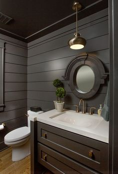 Floor-to-ceiling shiplap on the walls and dark grey, Sherwin Williams Black Fox paint, bring drama to the space.