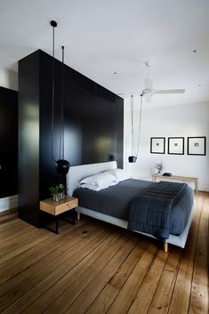 This black, white and modern bedroom features FLOS AIM lighting, hardwood floors and simple wall decor.