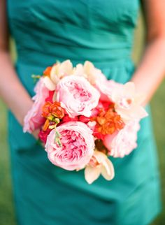 Bright, pink bouquets against teal blue dress