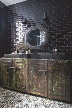 Dans la salle de bains, portes anciennes en métal, chinées par Laure, double vasque en céramique noire, miroir ancien et appliques noires en métal époxy mat