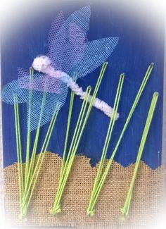 """""""Sudenkorentoja järvellä"""" (1.lk) 14x20cm lauta, joka hiottiin hiekkapaperilla ja maalattiin sin. valmisvärillä. Lisäksi tarvitaan nauloja, tarlattan-kangasta, askartelupunos, muovisilmät, lankaa sekä juutti/säkkikangasta."""