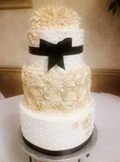 Champagne, Ivory, and Black wedding cake colors with ribbon and rosette textures
