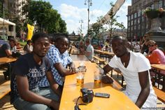 Three Congolese students have a beer in the fan zone in Kyiv. While some longtime residents stay away for fear of violence, visiting fans talk of a welcoming atmosphere. Photo by Tom Balmforth (RFE/RL)