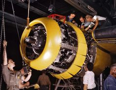 """July 1942. """"Production. B-25 bombers. Mounting a 1700-horsepower Wright Whirlwind engine to the firewall of a B-25 bomber. Fairfax bomber plant, Kansas City."""" 4x5 Kodachrome transparency by Alfred Palmer."""