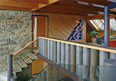 Interior view of a house with stone walls and lofted ceiling. The open staircase leads to a mezzanine level where the balustrading is built from water-filled columns which can have the water level altered to adjust the thermal mass of the building. Earthship Home, Passive Design, Thermal Mass, Thermal Comfort, Open Staircase, Buying A New Home, Design Strategy, Australian Homes, House Design