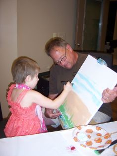 Dan Coleman, a member of our Educational Support Services team holds a canvas for little Maggie, a Wigs 4 Kids recipient who enjoys our art therapy classes.