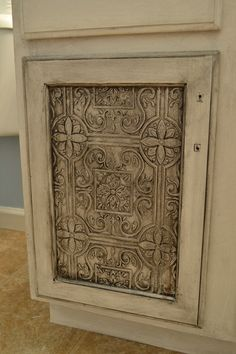 I am SO doing this for my cabinet doors !!! Faux Tin Tile wallpaper on Cabinet doors. Sprayed with Krylon's Bright Metallic Silver.The glazed by mixing 1/3 of black paint with 2/3 of Ralphs Lauren's glaze to paint over the door.