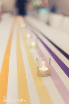 Yellow + purple ribbon & candle table decoration