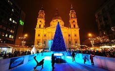 Children skate on an ice rink around a Christmas tree at a Christmas market in front of the St Stephan Basilica in Budapest – photo by Attila Kisbenedek