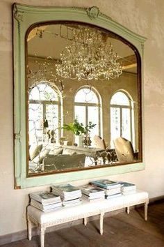 Old-world mirror and a huge one at that. Perfectly placed to reflect the arched glass doors and capitalize on all the natural light. In a Belgian mansion via Cococozy blog.
