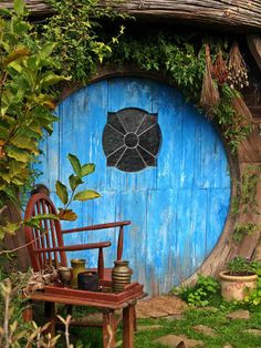 Enchanting blue circular door (not sure it opens) in a garden.  Love the leaded glass window.