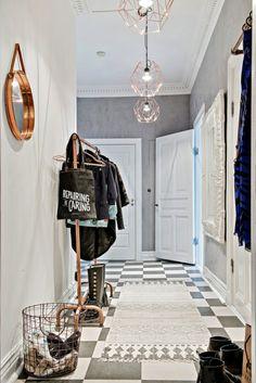 miedziany ażurowy kosz,miedziane okragłe lustro ,miedziane lampy druciane ,skandynawski dywanik w biało-szarym przedpokoju