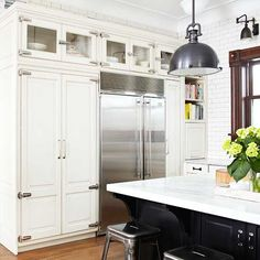 It makes sense to store less frequently used items, such as serving dishes, in out-of-the-way upper cabinets. But if your pieces are display worthy, opt for glass-front upper cabinets. Here, the glass fronts contrast the surrounding white cabinets and cool finish of the large stainless-steel refrigerator to give the bank of cabinets an airy look.