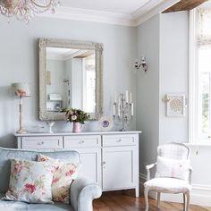 Inspiração para sala romantica: piso de madeira escura, paredes em tons pastéis, móveis brancos e objetos de decoração delicados.