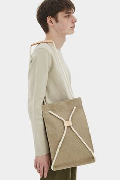 Pocket bag can be worn as a sack or as a shoulder bag. To transform it, simply pull the string. It features a 100% linen lininig, one interior pocket, magnetic