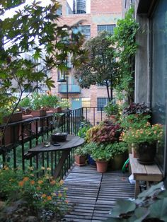 kleiner Balkon gestalten einfacher halbkreisförmiger Tisch viele grüne Pflanzen - Holzboden