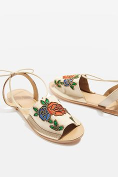 Add an eclectic feel to your summer sandals. This two-party style in black features gold bead embroidery to the toe strap and ankle tie detail.
