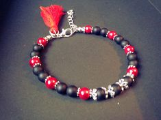 Bracelet femme fait main composé de perles en onyx mat, de perles en verres nacrées rouges, de perles en métaux (sans nickel) et dun pompon rouge. Le bracelet est ajustable grâce à sa chainette. Il mesure 18cm au plus court et 22cm au plus long. Envoyé avec un emballage pret à offrir. FRAIS, très beau