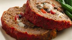 Cut slices of this juicy meatloaf, intensely flavored with herbs and prepared roasted peppers, to reveal a luscious center of melted cheeses.