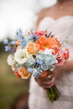 Blue hydrangea, thistle and delphinium are accented by coraly-peach gerbera daisies and roses!
