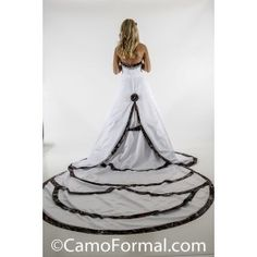 "Scalloped Camo Trimmed Wedding Gown with Camo Accented Detachable Cathedral Train. Strapless Wedding Gown with Top Band accented with heavy crystal and rhinestone trim. Sizes 2-30. Approximately 110"" fromt top of dress to end of train when attached to lower skirt. Detachable Train Included. Shown in White Satin and Mossy Oak New Breakup. Available in many satin colors and all camo patterns. Made in the USA."