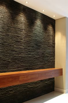 Dark textured stone (in this specific pattern) against the lighting and cherry wood 10 fantastic walls to inspire you (From Justwords)