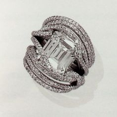 """JAR Paris. A SINGLE-STONE DIAMOND RING, BY JAR. Set with a rectangular-cut diamond entwined in """"diamond thread"""" hoops, mounted in platinum, approximate size 2½. By JAR. Price Realized $74,562 / Estimate $54,557 - $72,743 [C. MAGNIFICENT JEWELS - 18 November 1998 - Geneva] #JAR  #JARParis #JoelArthurRosenthal"""
