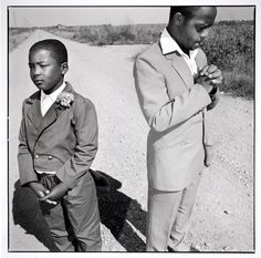Mary Ellen Mark  Man praying and a boy standing on a dirt road