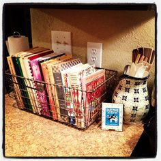 Cookbook organization for the visual person. I love wire baskets!