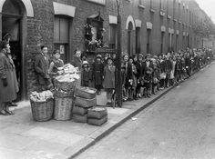 Children waiting for the 'farthing bundles' at the Fern Street settlement, 1934