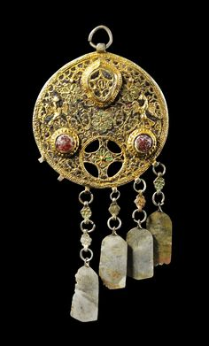 Round disk-pendant with four pendilias and enamel-inlays made of gilded silver. On the back engraved decor and inscription, 14th century.