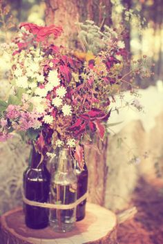 bottles gathered with twine to create large floral arrangement...wildfowers!