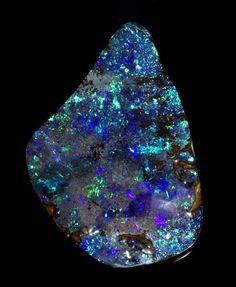 "Exceptionally Fine and Large Boulder Opal  Queensland, Australia   This is an extraordinary boulder opal both in terms of its size but also due to the vividness and strength of its color. Contour polished to reveal the gem-quality blue and green seam of opalization upon its rich brown ironstone matrix. This is a large, yet wearable opal sure to make a ""statement piece"" pendant; and a durable one at that, due to the stability provided by the ironstone matrix."
